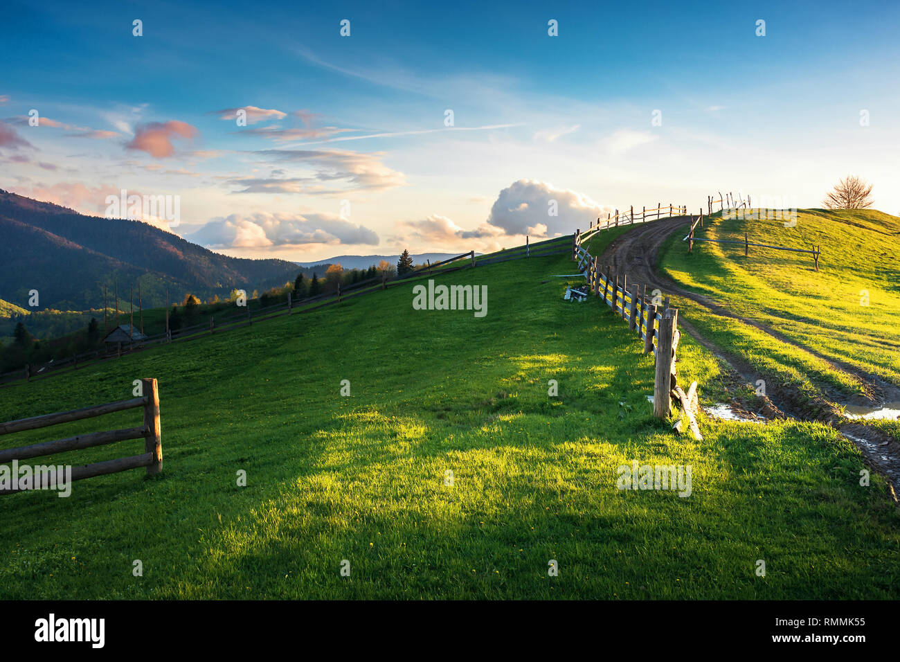 beautiful countryside scenery in mountains. fence on the grassy field. country road uphill the knoll. wonderful springtime weather at sunset with redd - Stock Image