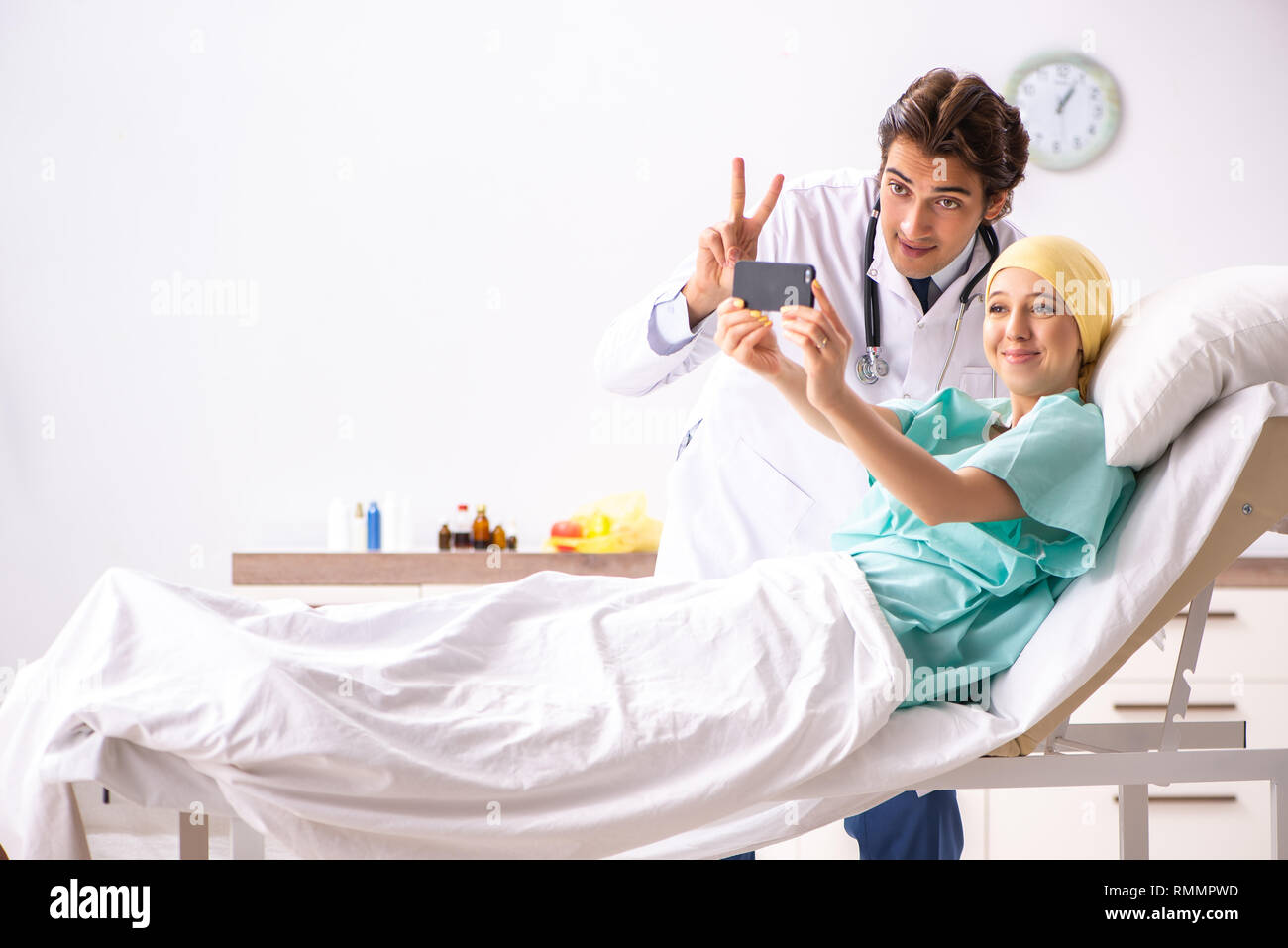 Young handsome doctor visiting female oncology patient - Stock Image