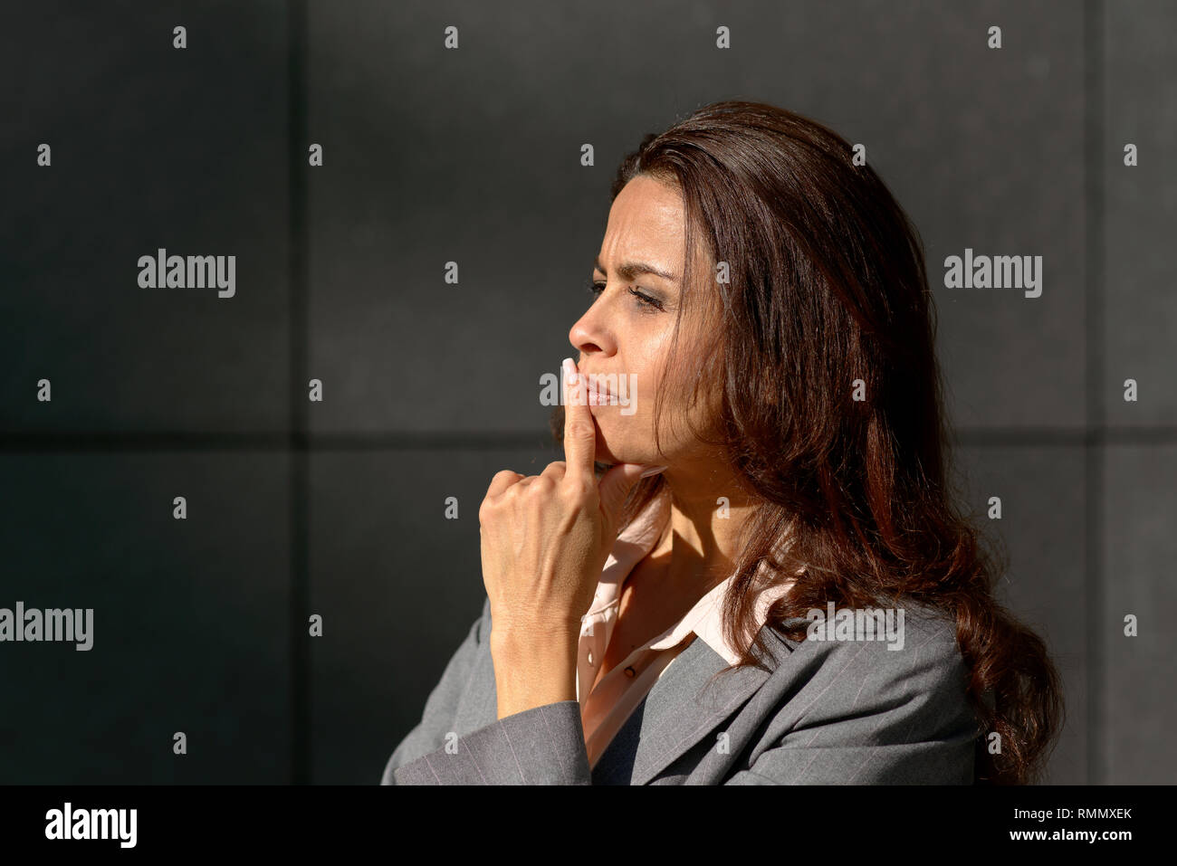 Thoughtful woman standing musing a problem with her finger to her lips in a profile view outdoors with copy space - Stock Image