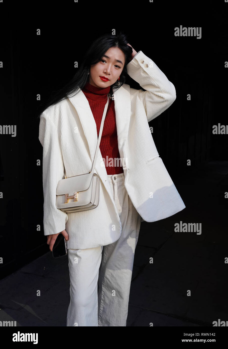 6a8fcc563bdd Fashionista dressed in white and wears a Hermes bag during the Autumn   Winter 2019 London