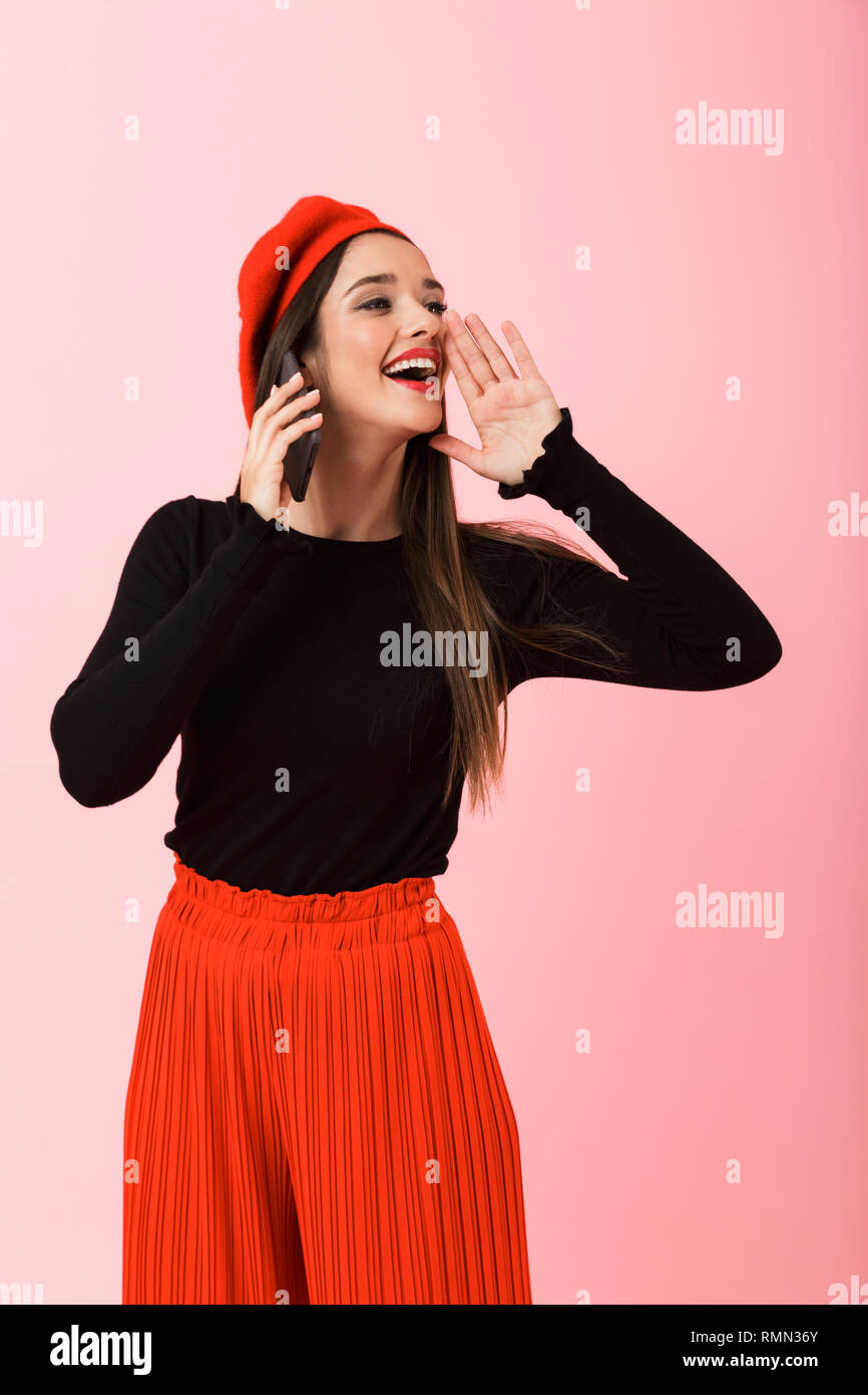 Portrait of a happy beautiful young woman wearing red beret standing isolated over pink background, talking on mobile phone loud - Stock Image
