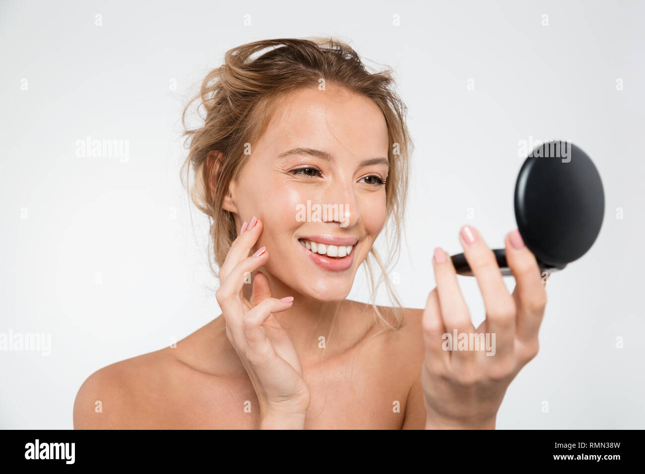 Beauty portrait of an attractive young blonde woman looking at the mirror isolated over white - Stock Image