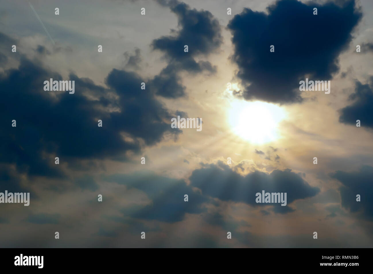 Crepuscular Rays Radiate From The Sun Partially Covered By A Bank Of Dark Stratocumulus Clouds Lingering In The Sky After A Summer Storm Stock Photo Alamy