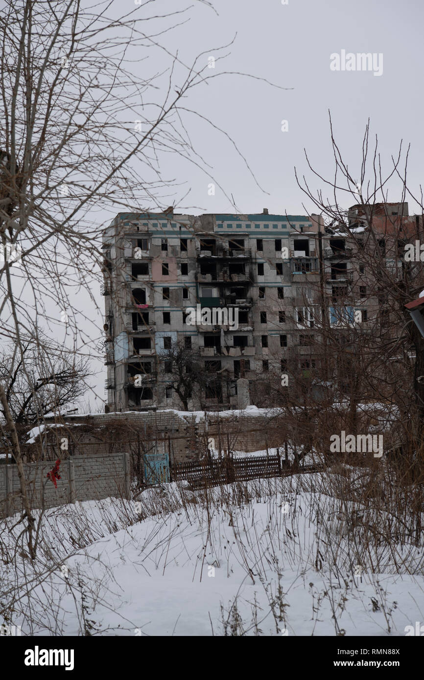A block of flats seen damaged by bombs close to the front line. The war between the Ukrainian army and the soldiers of the Donetsk Peoples Republic has cost the lives of 12,000 people and those who have been displaced exceed a million. It escalated in 2014. Despite a ceasefire in place, it is evident that death still occurs from predominantly, sniper, mortar and mines. The construction of trenches either side of no-man's land, (often only 100mt apart) have ensured a static yet aggressive confrontation. The Minsk ceasefire agreement and constant political turbulence has only made a stalemate an - Stock Image