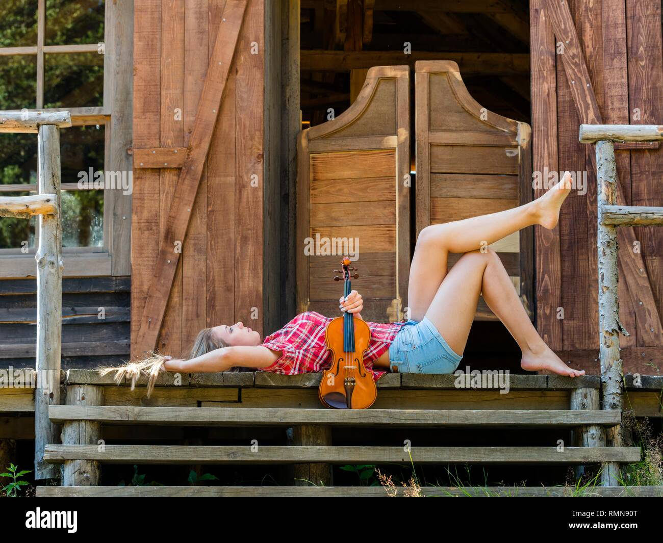 Pretty teen girl with violin musical instrument lying on back on porch of Western style saloon entrance wooden doors - Stock Image