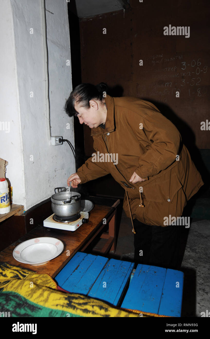 Alina Viktorovna seen making tea at an ex-soviet bomb shelter. The war between the Ukrainian army and the soldiers of the Donetsk Peoples Republic has cost the lives of 12,000 people and those who have been displaced exceed a million. It escalated in 2014. Despite a ceasefire in place, it is evident that death still occurs from predominantly, sniper, mortar and mines. The construction of trenches either side of no-man's land, (often only 100mt apart) have ensured a static yet aggressive confrontation. The Minsk ceasefire agreement and constant political turbulence has only made a stalemate and - Stock Image