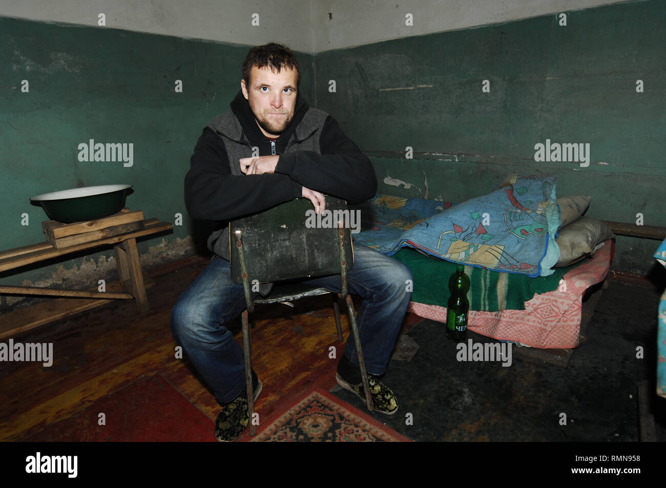 Andrei seen taking refuge in an underground ex-soviet bomb shelter. The war between the Ukrainian army and the soldiers of the Donetsk Peoples Republic has cost the lives of 12,000 people and those who have been displaced exceed a million. It escalated in 2014. Despite a ceasefire in place, it is evident that death still occurs from predominantly, sniper, mortar and mines. The construction of trenches either side of no-man's land, (often only 100mt apart) have ensured a static yet aggressive confrontation. The Minsk ceasefire agreement and constant political turbulence has only made a stalemat - Stock Image
