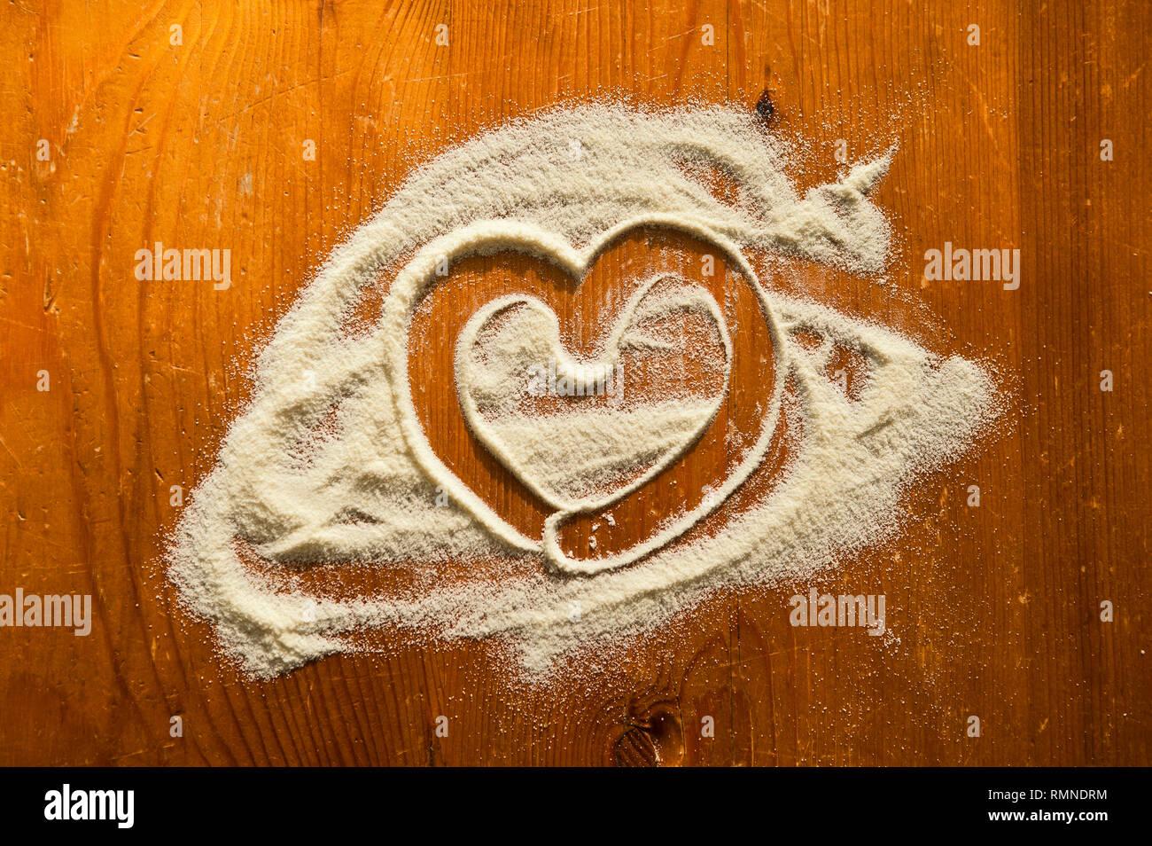 Auf einem roetlich-braunen Holztisch wurde in eine Pastamehlflaeche ein Herz gemalt. [(c) Dirk A. Friedrich - Stock Image