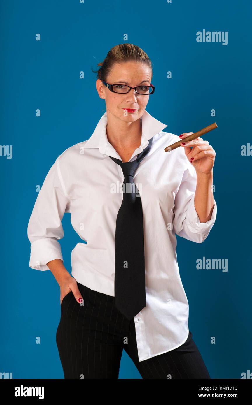 Dunkelblonde Frau steht vor tuerkiser Wand mit strenger Frisur traegt Maennerkleidung und haelt eine Zigarre in der linken Hand.  MR:YES PR:YES [(c) D - Stock Image