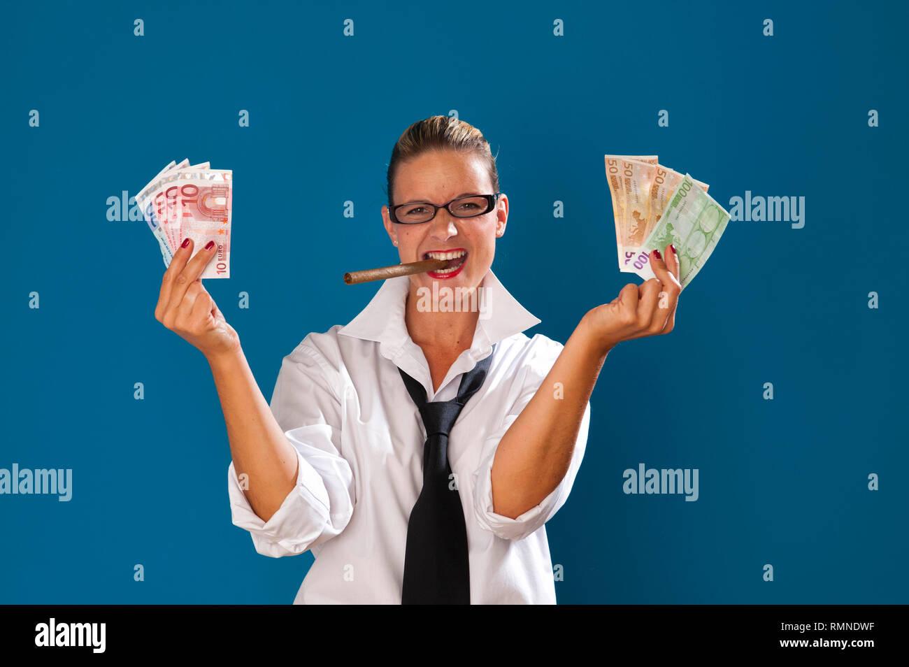 Dunkelblonde Frau steht vor tuerkiser Wand mit strenger Frisur traegt Maennerkleidung, Zigarre im Mund haelt Geldscheine in der Hand MR:YES PR:YES [(c - Stock Image