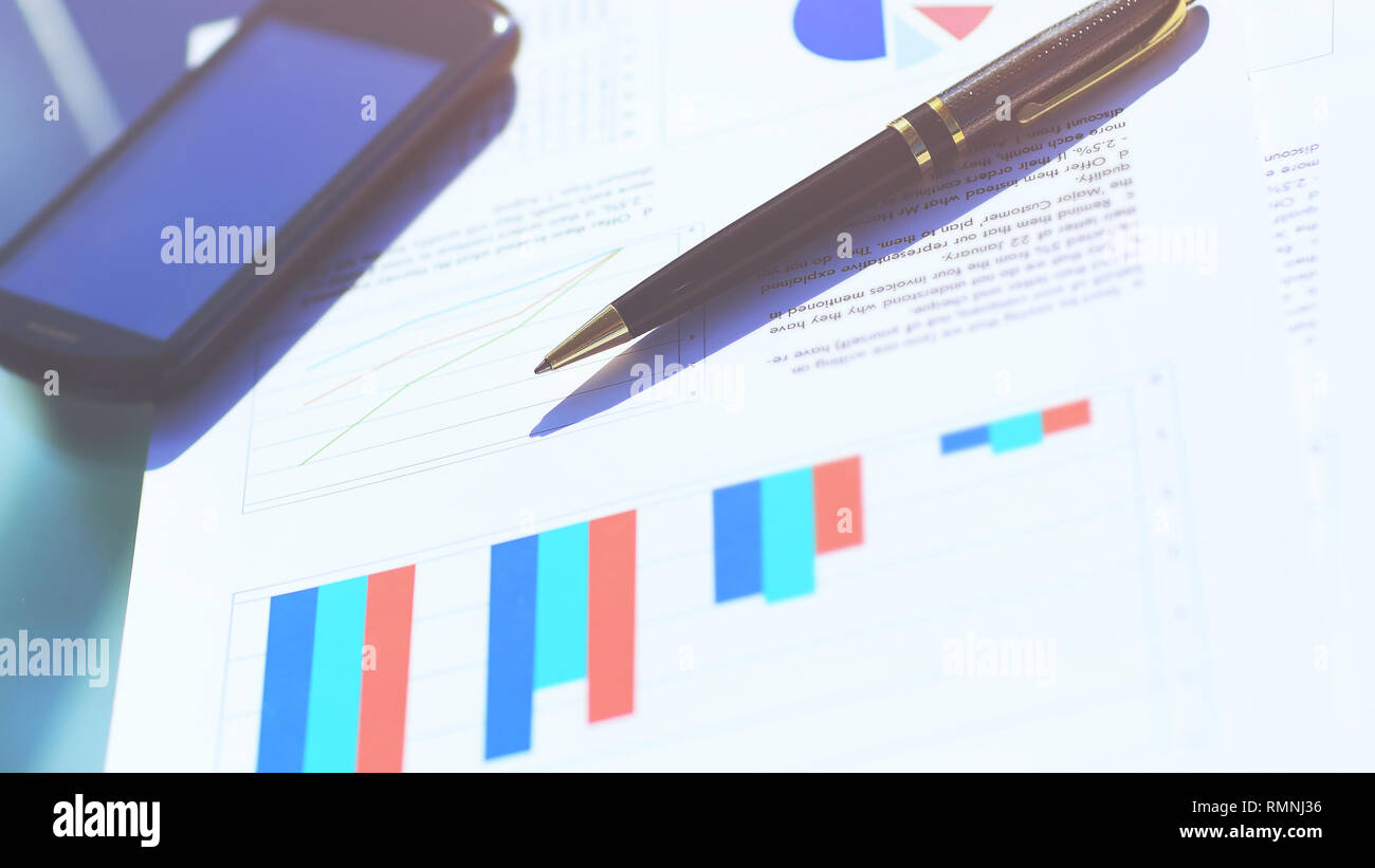Financial charts on the table with tablet and pen - Stock Image