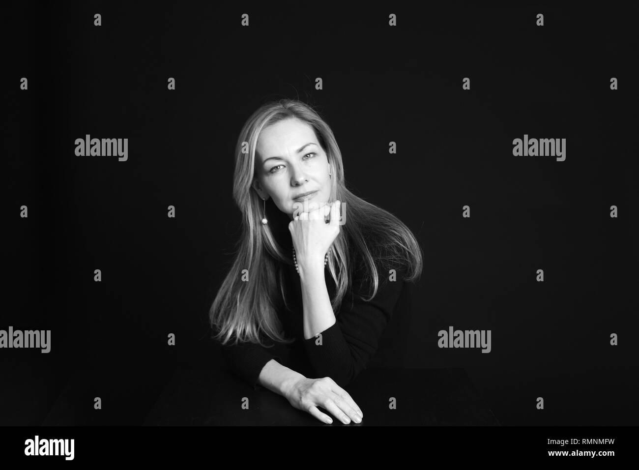 Close up studio portrait of a beautiful woman in the black dress against black background