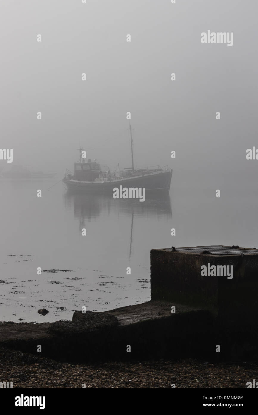 boats in the fog on calm water - Stock Image