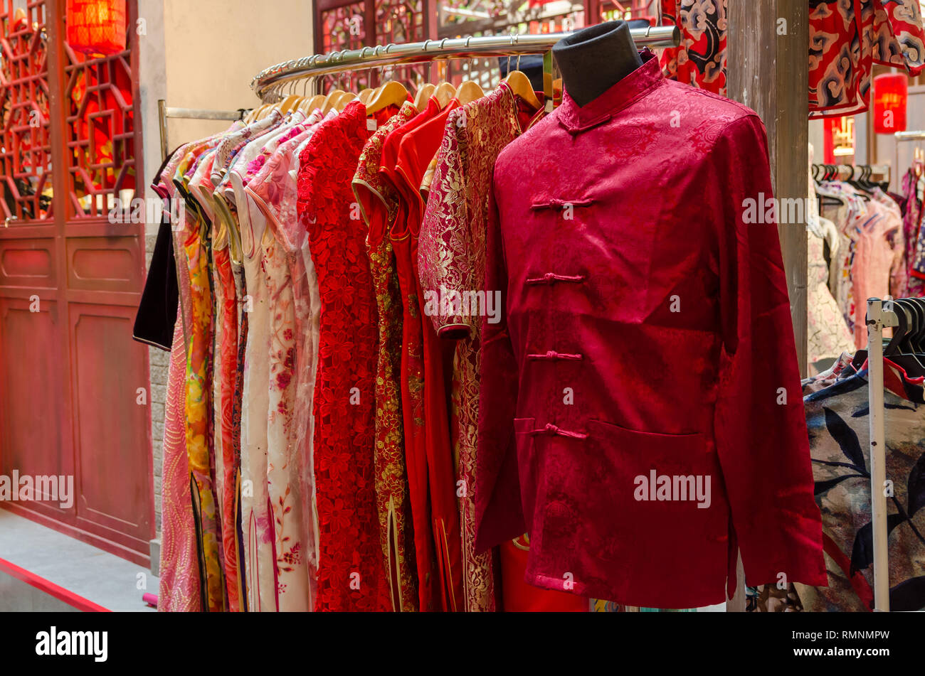 Colorful traditional chinese costumes hanging for sale during Chinese New Year. - Stock Image