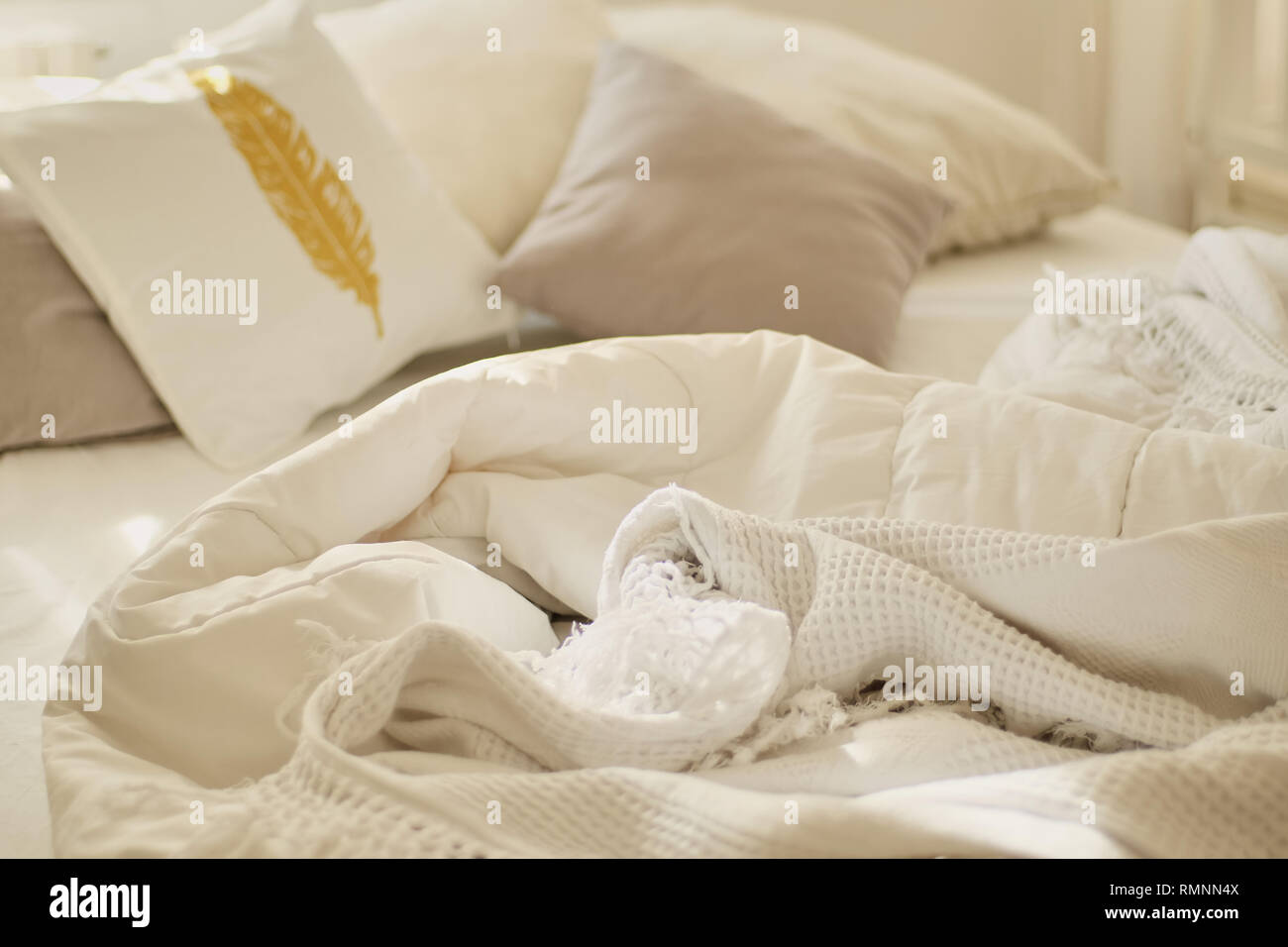 Messy bed. White pillow with blanket on bed unmade. Concept of relaxing after morning. With lighting window. Top view. - Stock Image