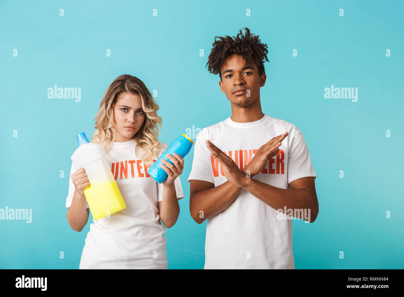 Angry confident multiethnic couple wearing volunteers t-shirt standing isolated over blue background, holding detergents, showing crossed hands gestur - Stock Image