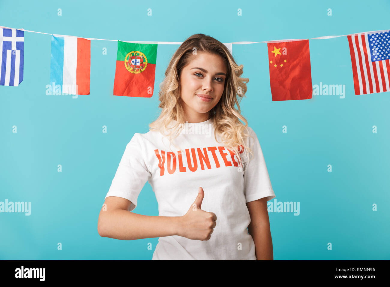 Portrait of a smiling young girl wearing voluteer t-shirt standing isolated over blue background, showing thumbs up - Stock Image