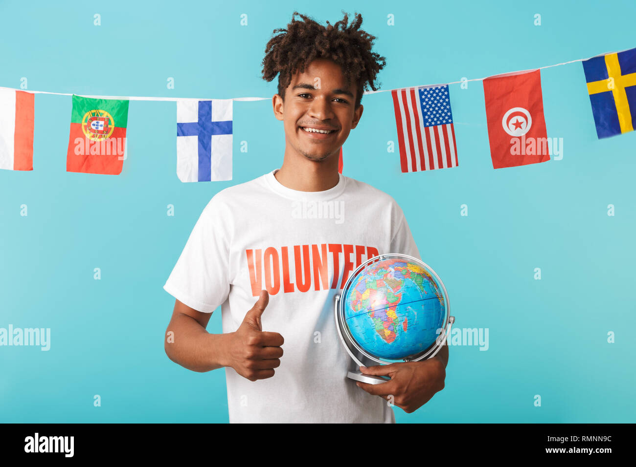 Portrait of a smiling young african man wearing voluteer t-shirt standing isolated over blue background, showing thumbs up - Stock Image
