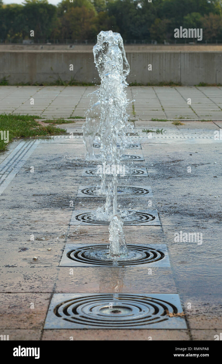 Several small ground fountains in one line - Stock Image