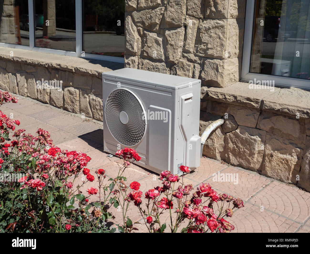 High efficiency modern AC-heater inverter unit, energy save solution-horizontal, outside a residential home Stock Photo