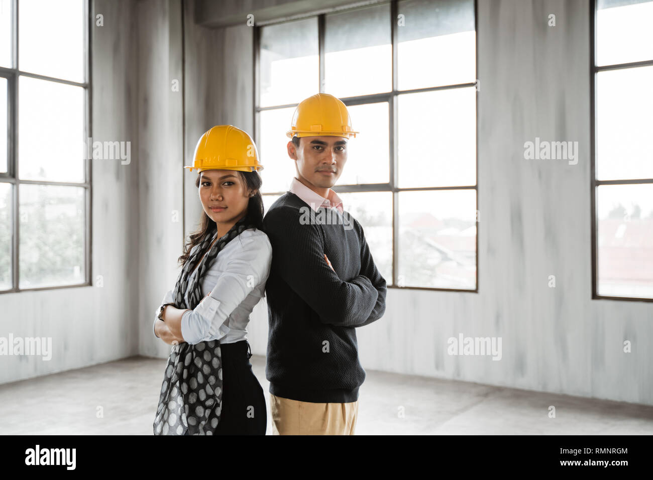 business team back to back crossed their arm and wearing hardhat looking at camera - Stock Image