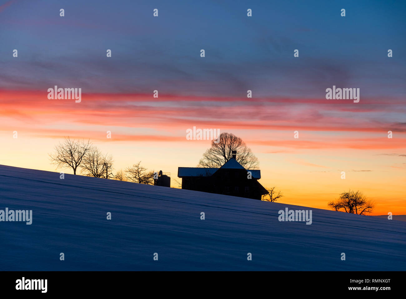 silhouette of a farm in Emmental at a winter sunset - Stock Image