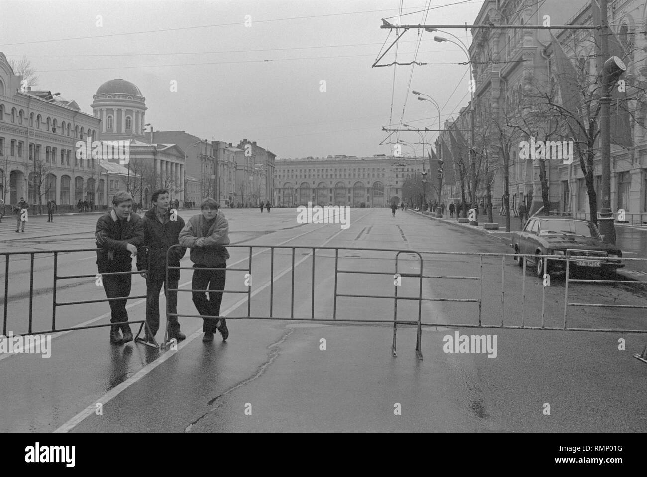 Moscow, USSR - November 7, 1990: Three young men stand by the fence at rally set by Moscow Association of voters, Democratic Russia movement and Democratic Platform without CPSU. - Stock Image