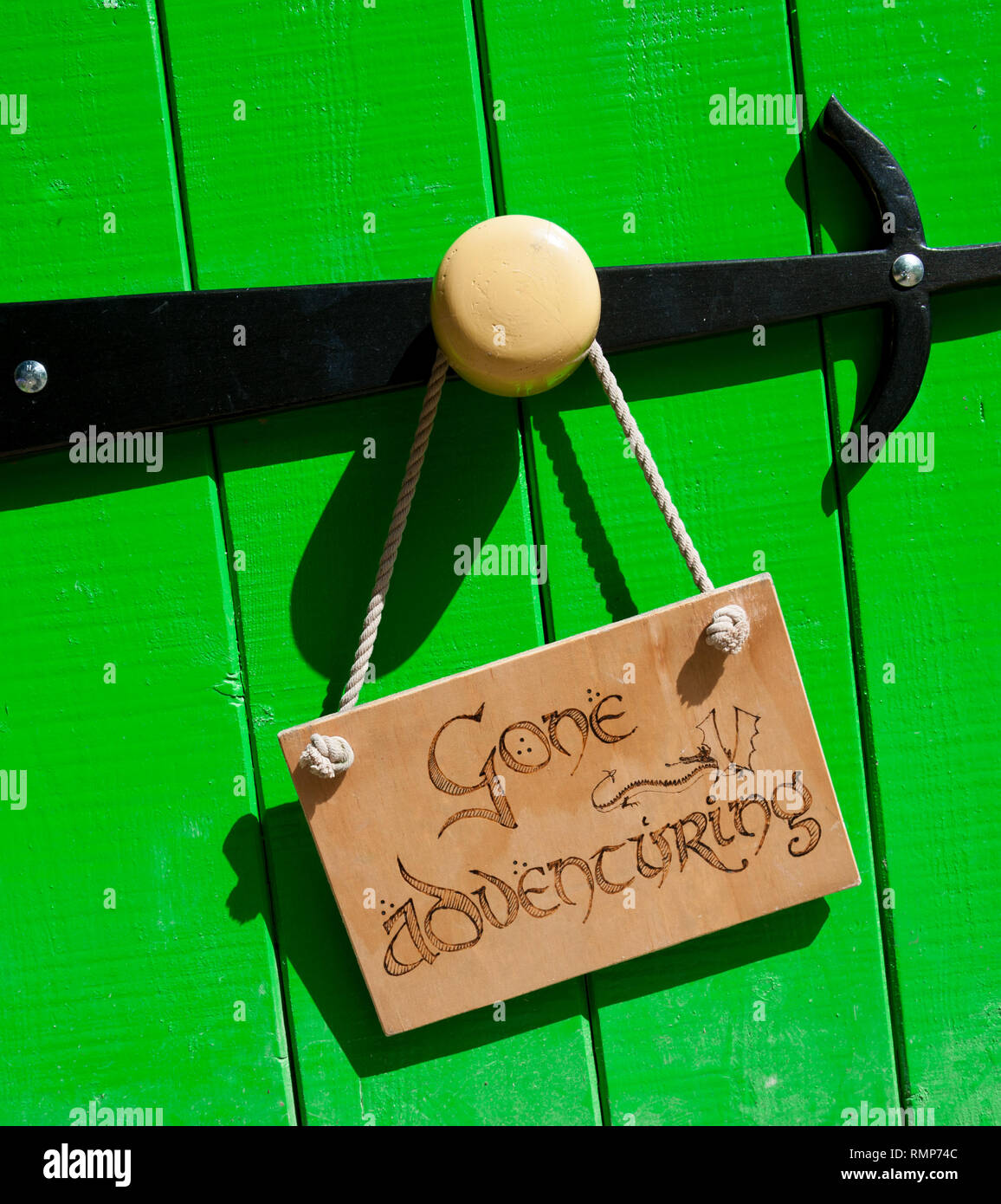 Green wooden door with large round knob and black hinge.  Gone Adventuring sign hung from door knob - Stock Image