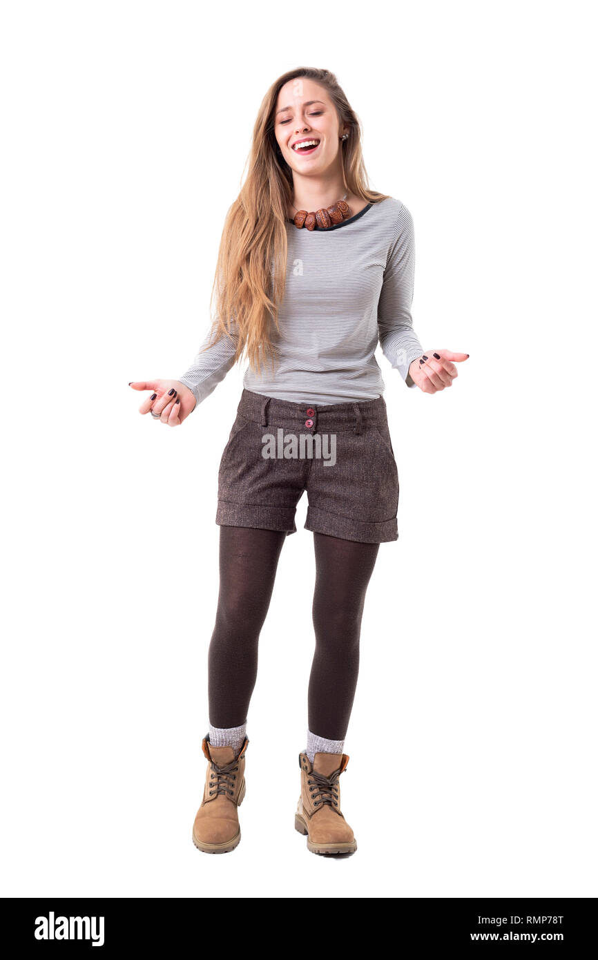 Confused young cute stylish woman laughing while talking with closed eyes. Full body isolated on white background. - Stock Image