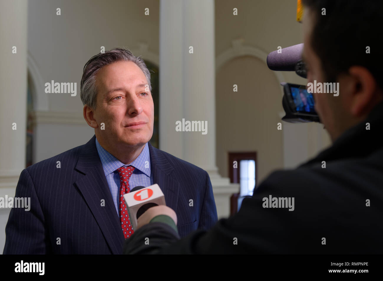 Mineola, New York, USA. 15th Feb, 2019. JON KAIMAN, Deputy County Executive in Suffolk, is interviewed by Verizon FIOS 1 news reporter after Kaiman spoke at NYS Senate Public Hearing on Climate, Community & Protection Act, Bill S7253, sponsored by Sen. Kaminsky, Chair of Senate Standing Committee on Environmental Conservation. This 3rd public hearing on bill to fight climate change was on Long Island. Credit: Ann Parry/ZUMA Wire/Alamy Live News Stock Photo