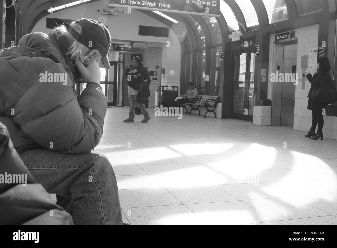 Lonely man in train station in Summit, New Jersey, seemingly forlorn. - Stock Image
