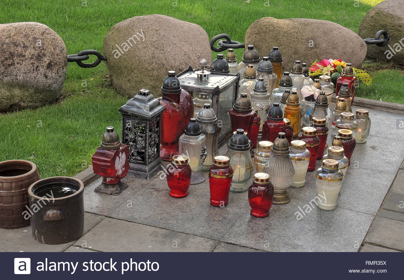 Votive candles burn near the grave of Blessed Fr Jerzy Popieluszko on the grounds of the Church Of St Stanislaus Kostka, Warsaw, Poland. - Stock Image