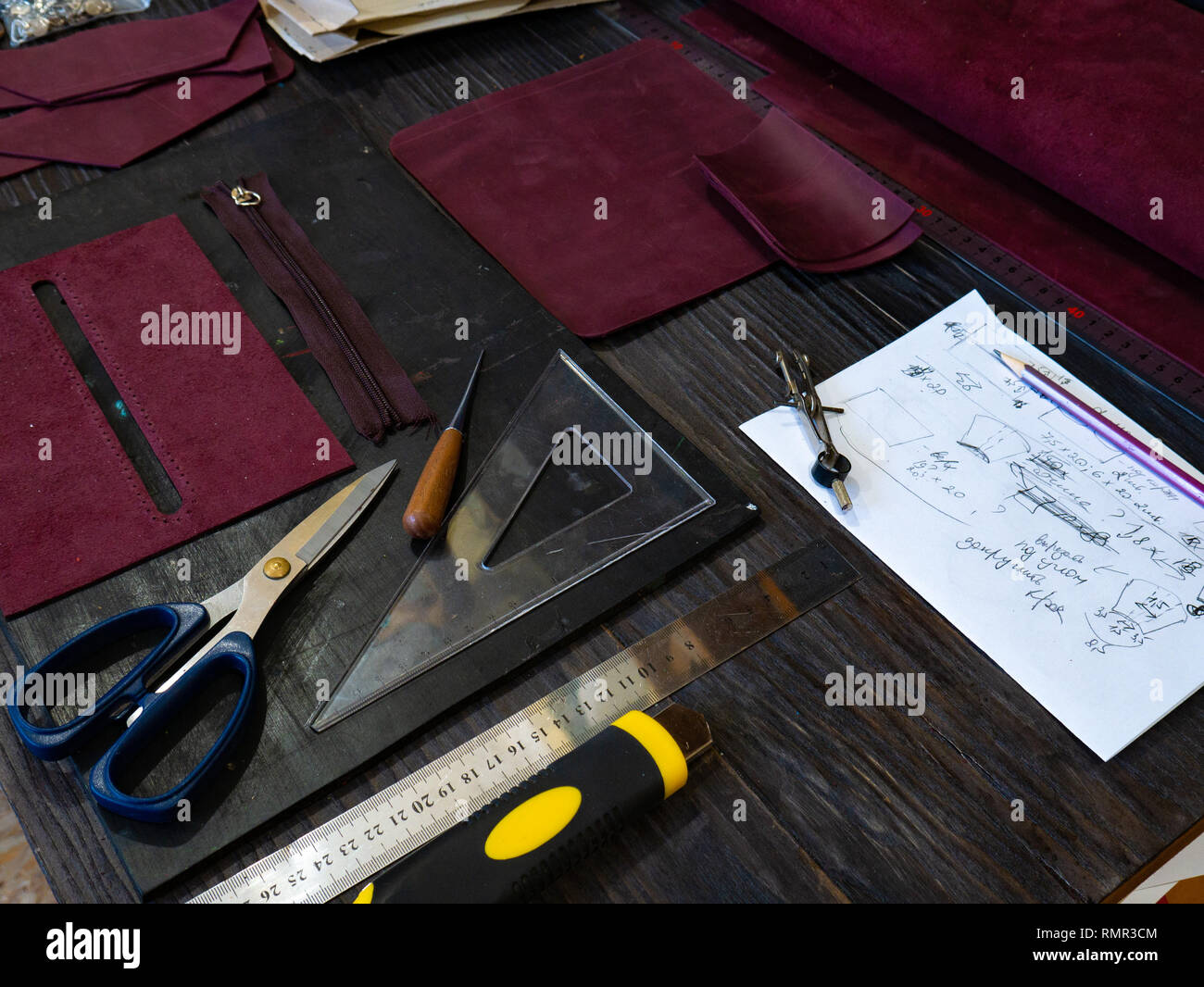 Tools for leather crafting and pieces of Marsala leather Manufacture of leather - Stock Image
