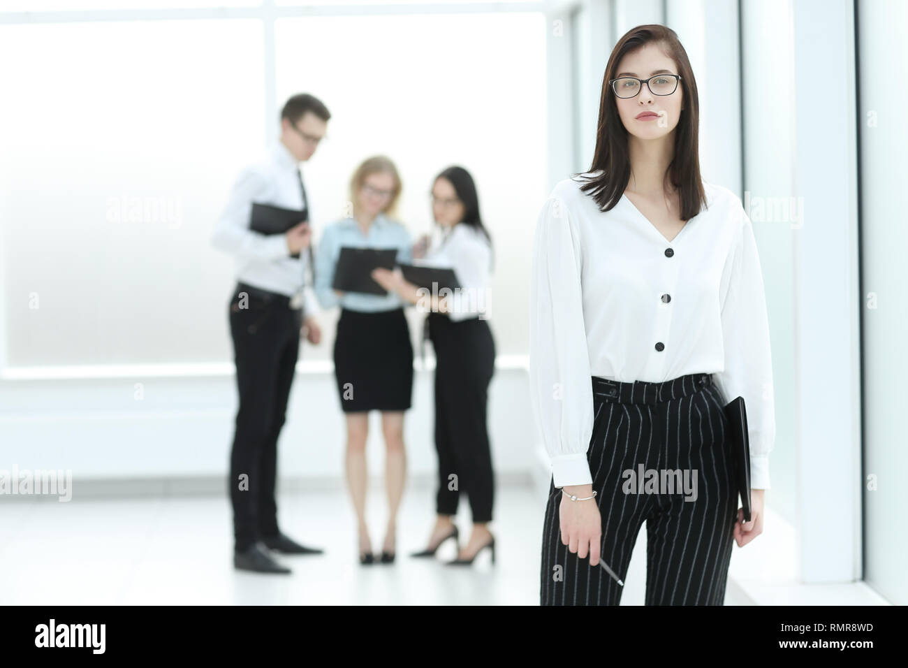 a65772f2bb9 Executive business woman standing in office lobby Stock Photo ...
