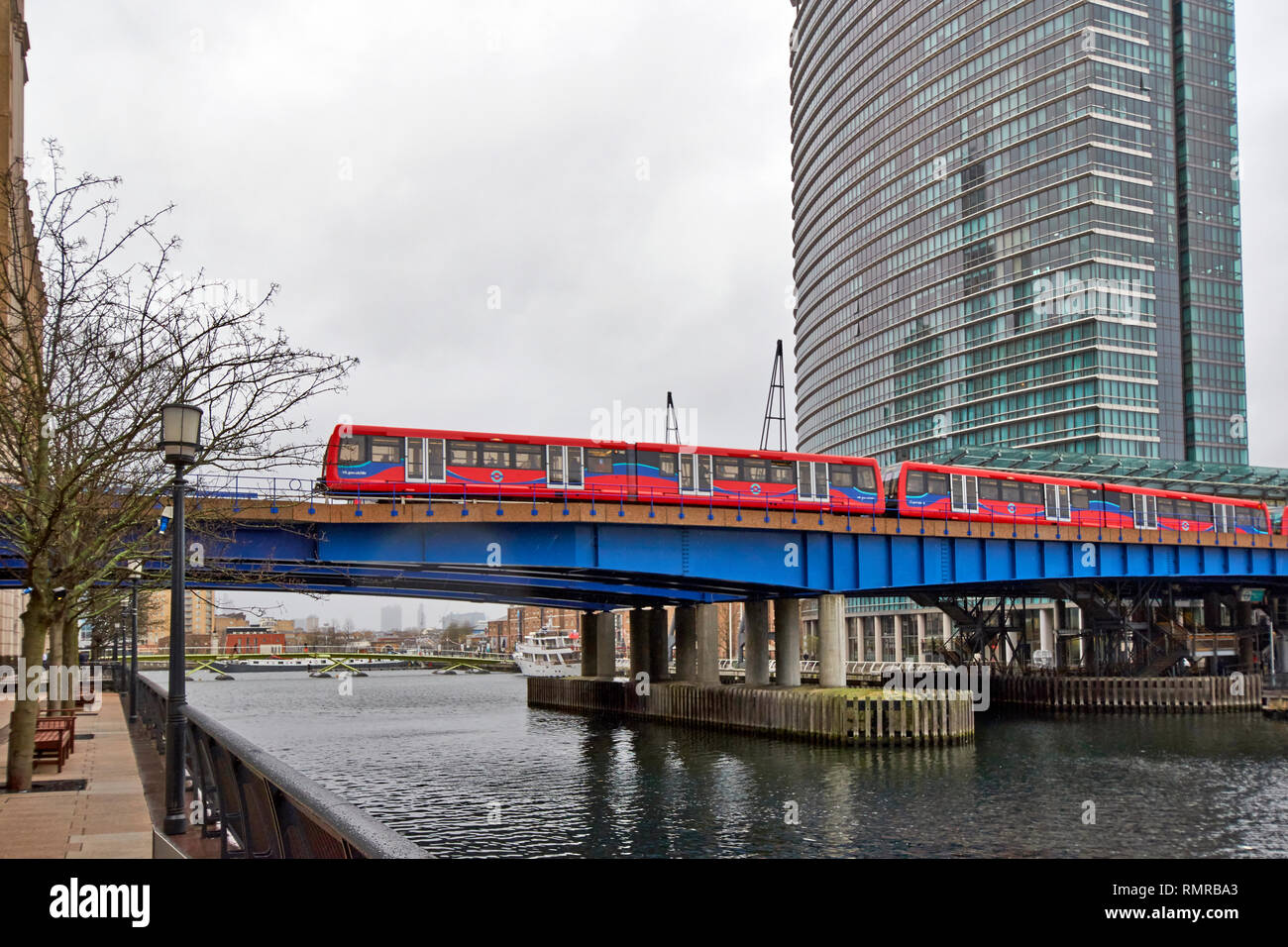 LONDON CANARY WHARF TFL RED TRAIN CROSSING THE NORTH DOCK - Stock Image