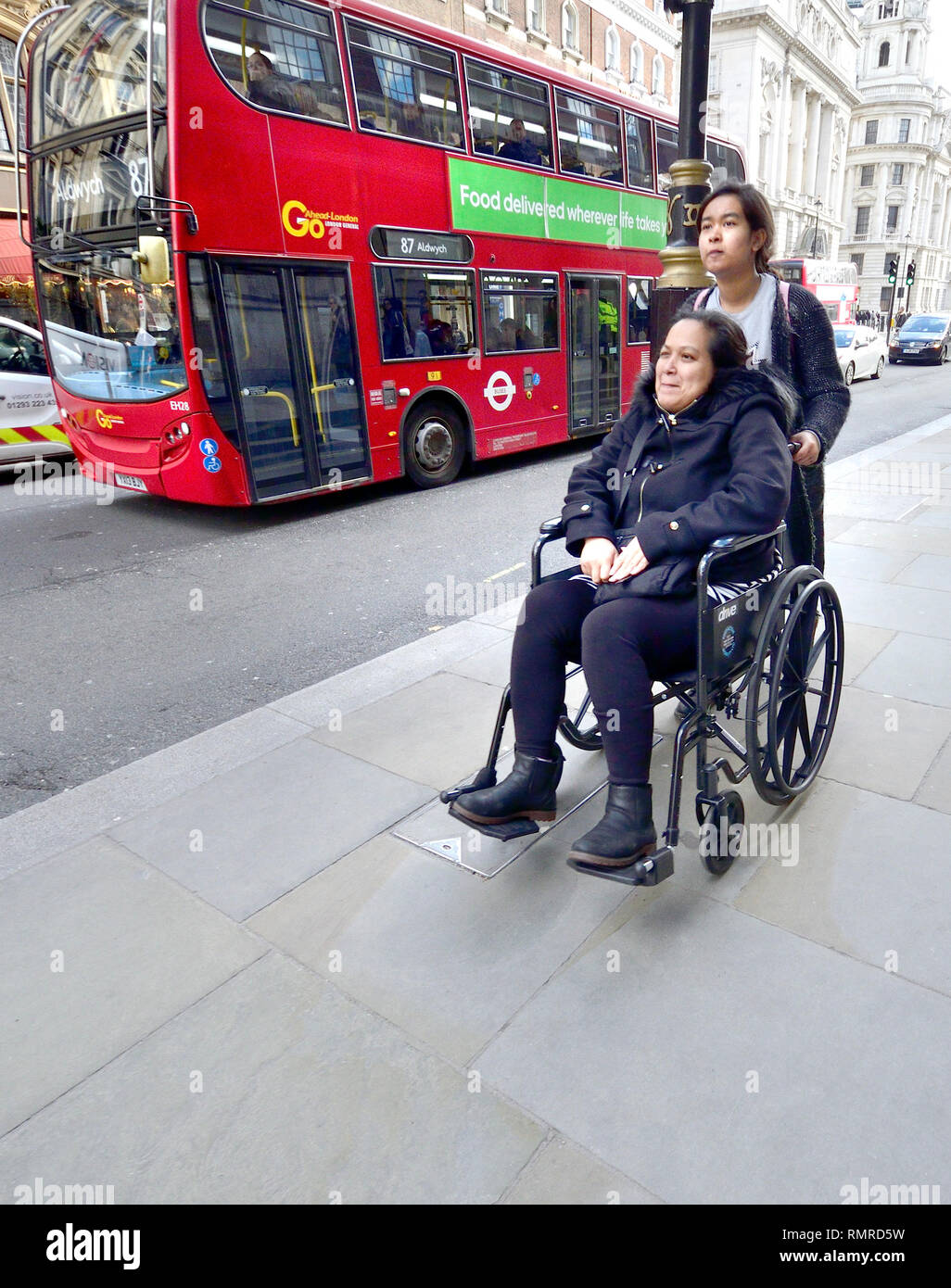 London, England, UK. Woman being pushed in a wheelchair in Whitehall as a bus passes - Stock Image