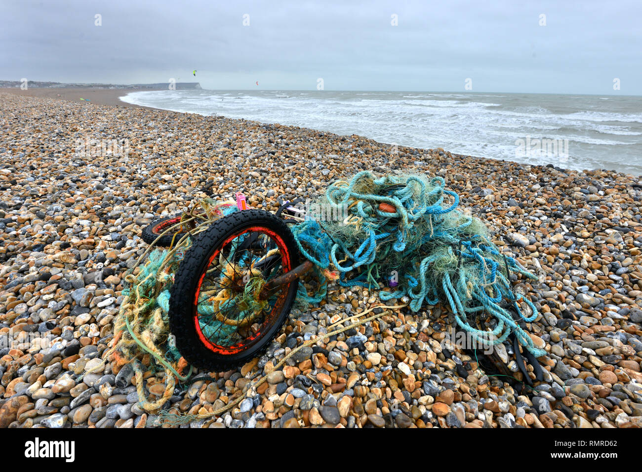Old bike tangled in a plastic fishing net, discarded on a beach, East Sussex, UK - Stock Image