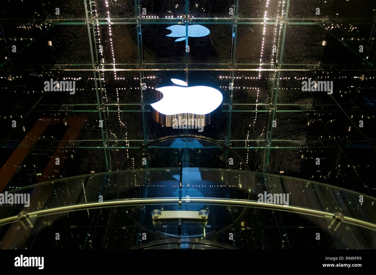 The lighted white logo of Apple at a flagship store in New York City's 5th Avenue at night. Stock Photo