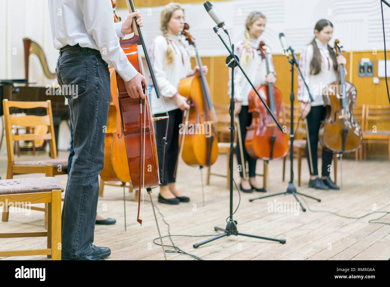 Children's violin ensemble. Children with violins on stage. Children's initiative, small talents. Early child development. Blurred. - Stock Image