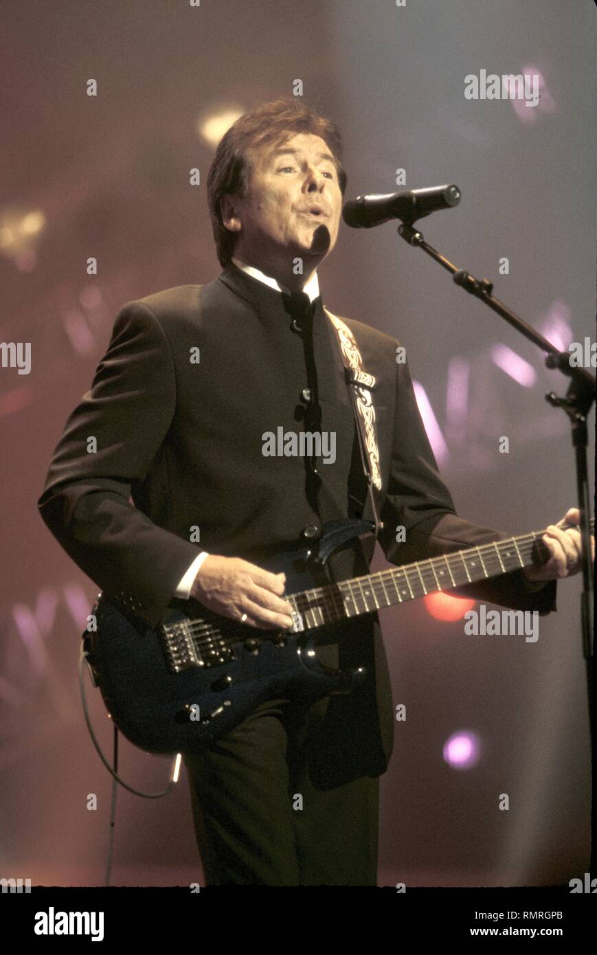 The singer and guitarist of the British rock band The Searchers is shown performing on stage during a 'live' concert appearance. - Stock Image