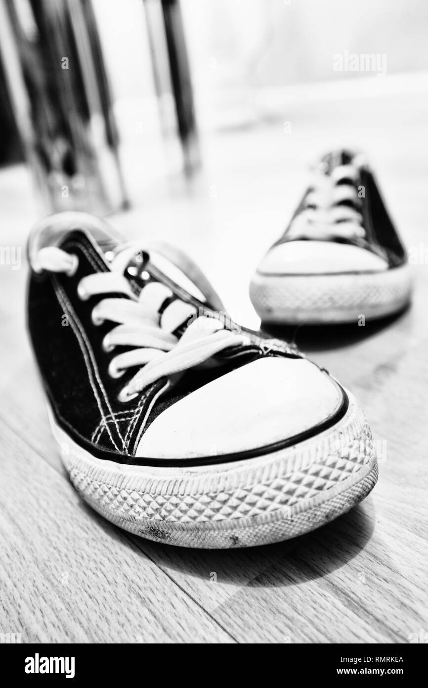 Black and white photo of trendy trainers shoes with laces on the floor. Taken in vertical format - Stock Image