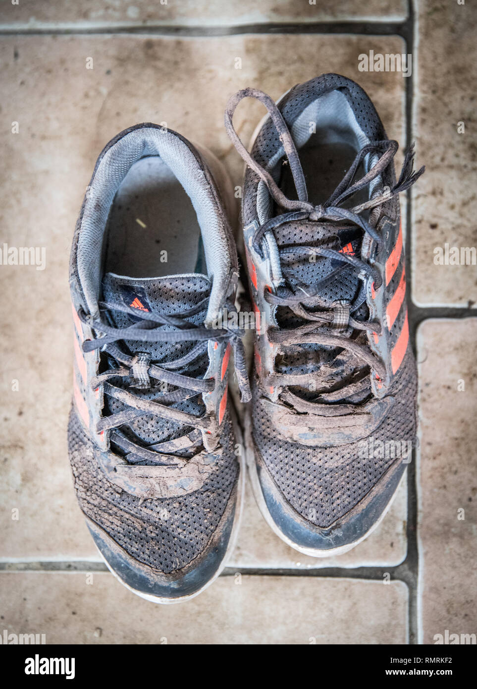Vertical shot of a diry worn out pair of muddy trainers sneakers shoes, - Stock Image