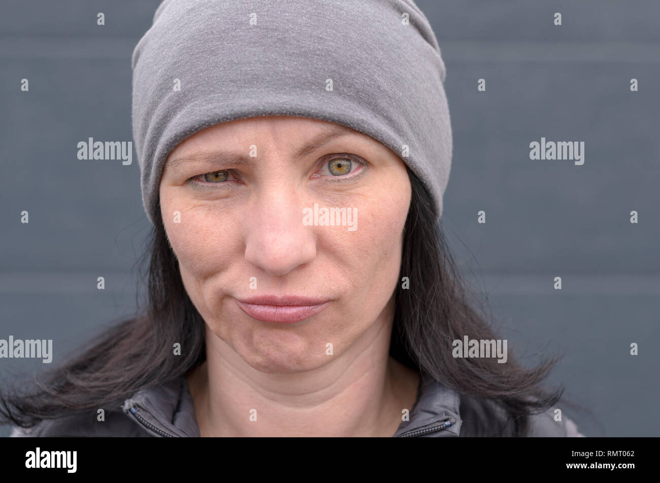 Dubious woman wearing a knitted grey winter cap grimacing and looking at camera with a pensive expression in a close up cropped portrait - Stock Image
