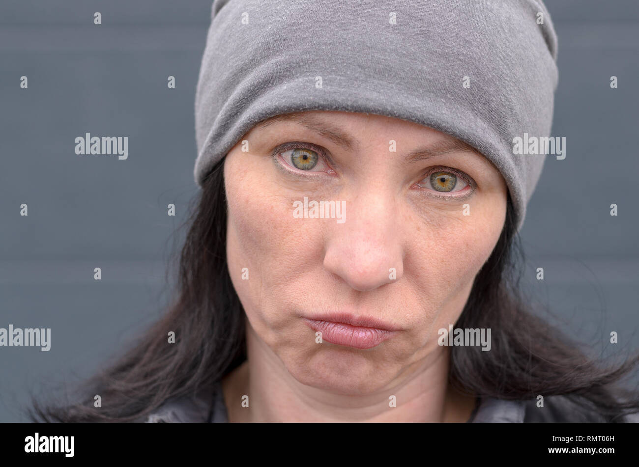 Dubious woman wearing a knitted grey winter cap grimacing and looking at camera with a sad expression in a close up cropped portrait - Stock Image