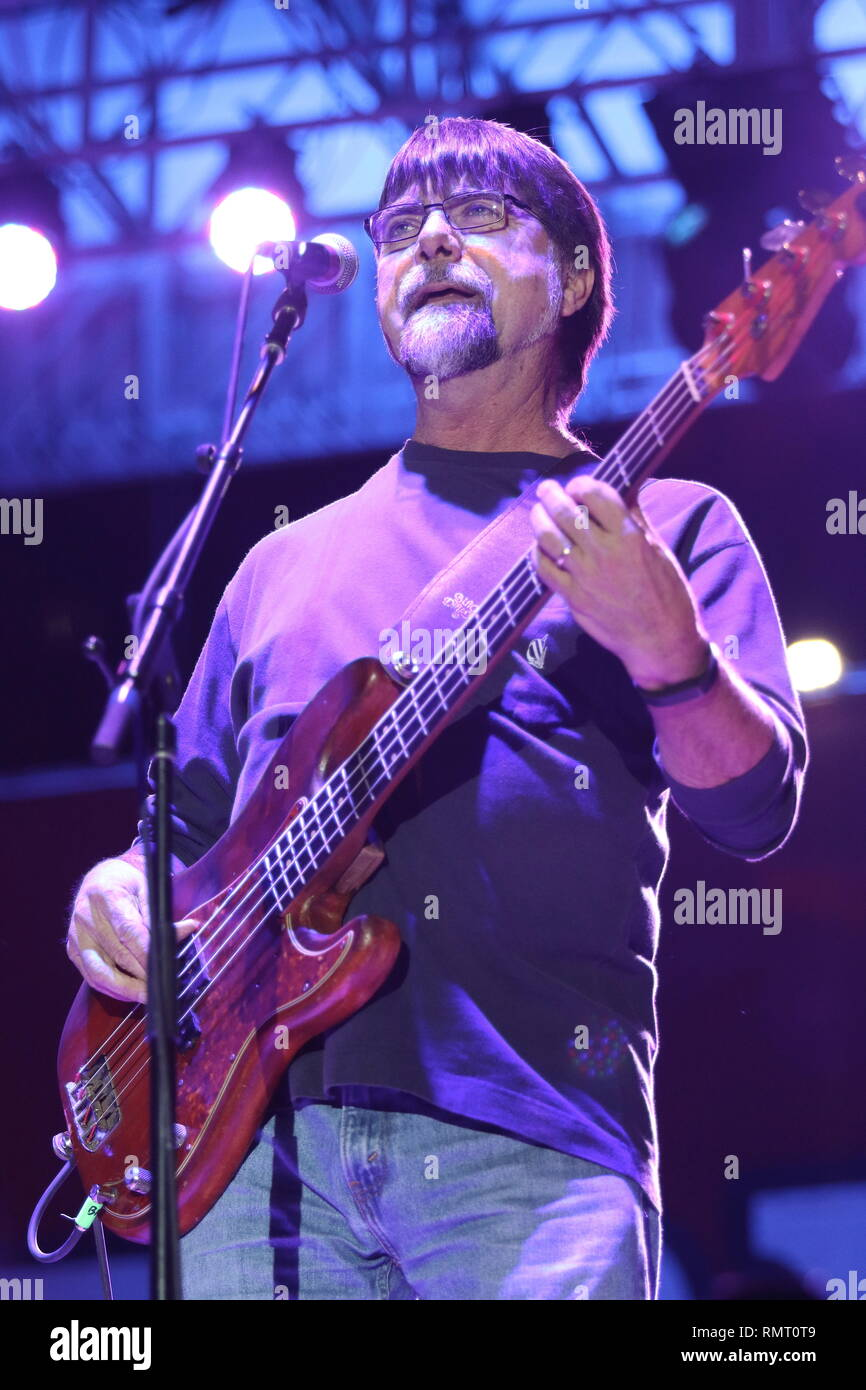 """Bass guitarist Teddy Gentry is shown performing on stage during a """"live"""" concert appearance with Alabama. Stock Photo"""
