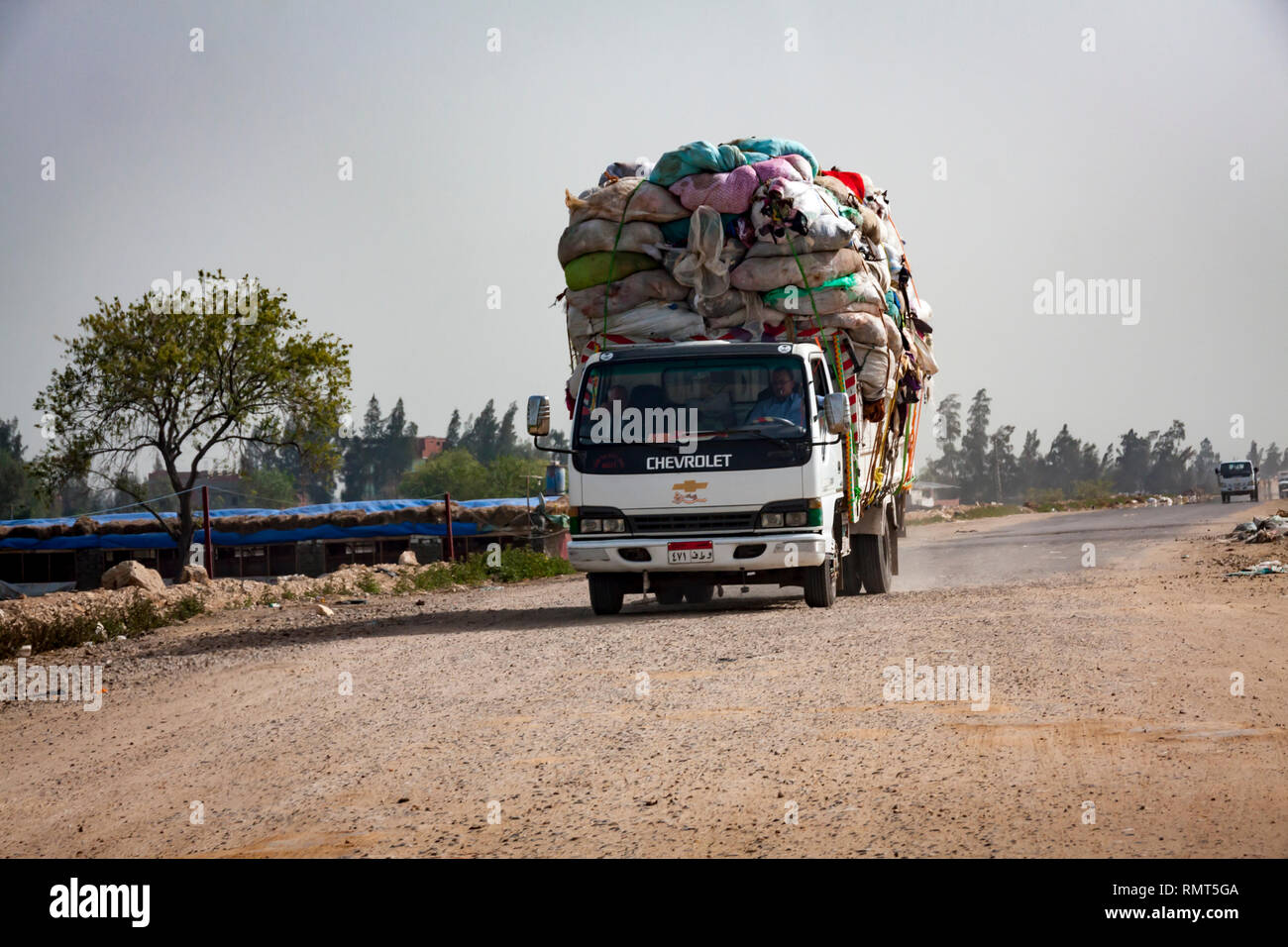 Kafr-El-Sheikh, Egypt - 3 March 2014: A truck overloaded with garbage bags passing through farmland heading for landfill site in Egypt. - Stock Image