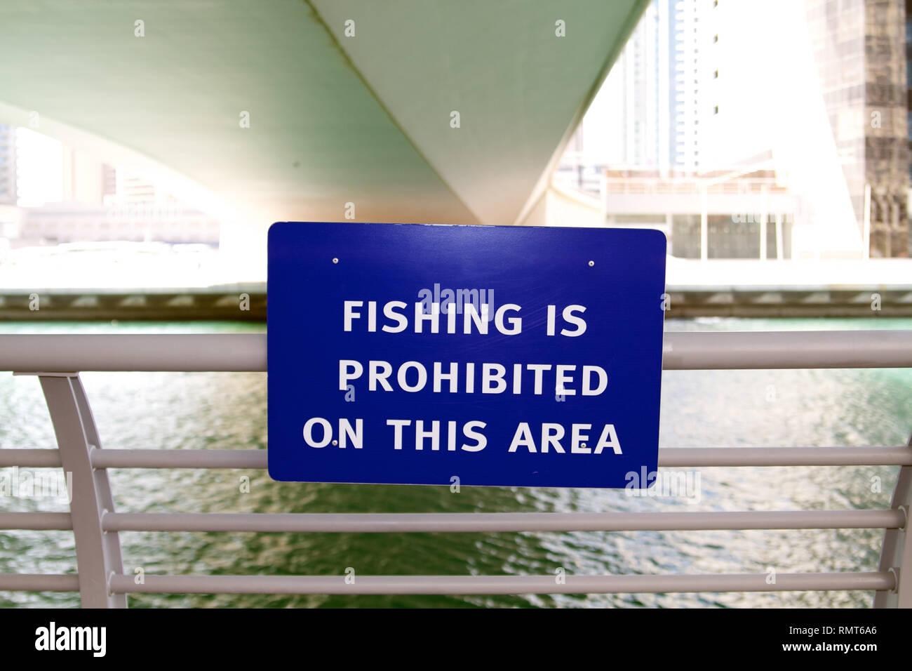 Dubai-Fishing is prohibited on this area blue warning plate at Marina walk - Stock Image