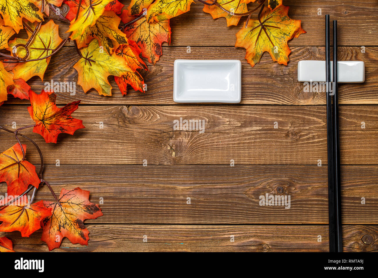 Wooden table with maple leaves - Stock Image