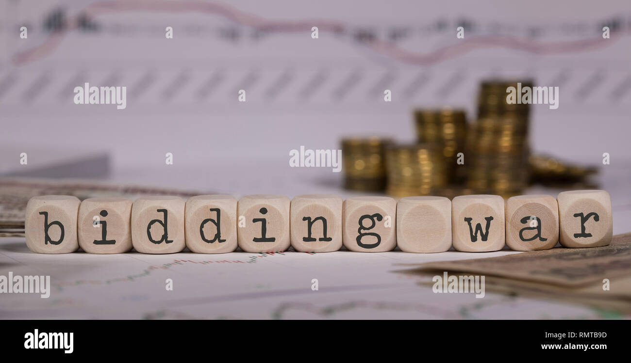 Words BIDDING WAR composed of wooden letter. Stacks of coins in the background. Closeup Stock Photo