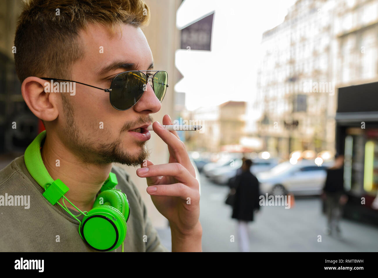 Young handsome man with green headphones and sunglasses enjoying a cigarette in the street. - Stock Image